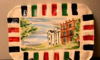 Beautiful, hand painted ceramic dish featuring the Nisbet House. These unique pieces are created by member Janet Nisbett and will look great as a trivet or table art.  Each piece is approximately 5 inches high x 7-1/4 inches wide. Stand not included.